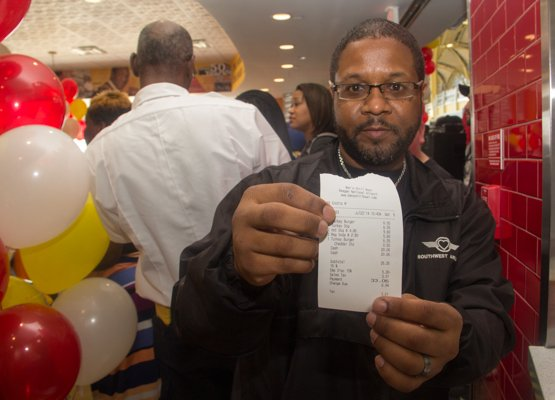 Southwest Airlines employee Alan Pauls shows off his receipt as the first patron at Ben's Chili Bowl's newest location at National Airport in Fairfax, Va., on Wed., July 23.
