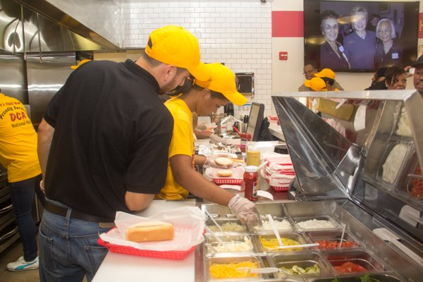 Ben's Chili Bowl employees prepare food during the opening of the restaurant's newest location at National Airport in Arlington, Va., on Wed., July 23.