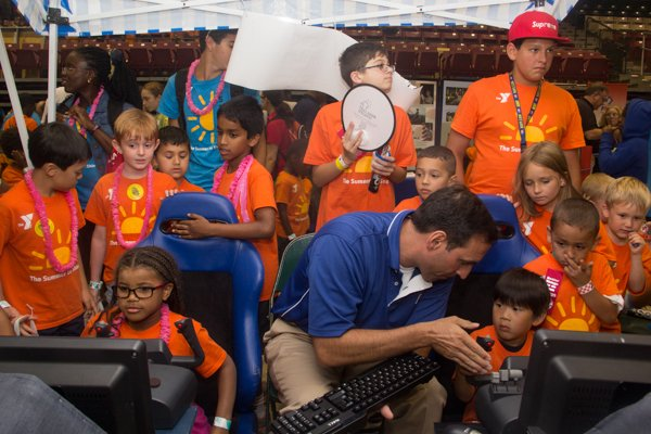 Chris Marchioni of the Air Force Academy helps children with flight simulation activities during the Thingamajig Conference hosted by the YMCA of Metropolitan Washington at Show Place Arena in Upper Marlboro, Md., on Thurs., July 24.
