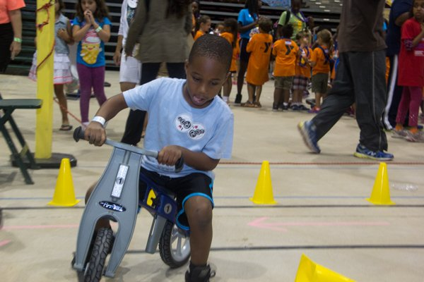 Quincy Kennard navigates a small bike on an obstacle course at the Thingamajig Conference hosted by the YMCA of Metropolitan Washington at Show Place Arena in Upper Marlboro, Md., on Thurs., July 24.