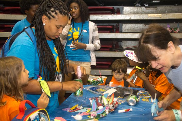 Volunteers help children make rabbits out of soda cans at the Thingamajig Conference hosted by the YMCA of Metropolitan Washington at Show Place Arena in Upper Marlboro, Md., on Thurs., July 24.