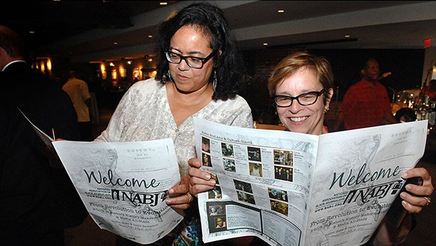 Globe Community Relations chief, Ellen Clegg (r) looks over the newsprint that Joyce Ferriabough Bolling created about Boston's Black media history slide show she produced with graphic design and layout by Sydney Janey for the Boston Globe-Boston Association of Black Journalists bash on Thursday at Fenway Park. The Bash welcomed the National Association of Black Journalists to Boston and was attended by more than 700 people. (Photo by Don West.)