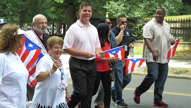 City Councilor Tito Jackson, Mayor Martin Walsh, former City Councilor Felix D. Arroyo and parade festival organizer Carmen Colombani  march by the Common.