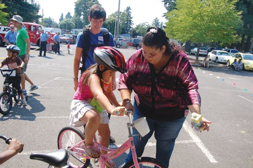 A mother guides her daughter on the cycling course at the Community Cycling Center's 'Bikes for Kids' festivities Saturday at the Rockwood Boys and Girls Club at 165th and Stark in Gresham. The non-profit cycling center gave away 100 brand new bikes to deserving children during the event.