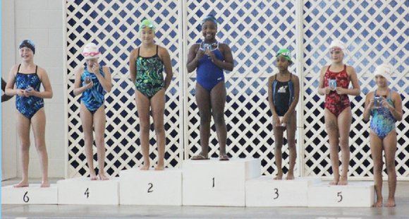 Eight-year-old teammates Jayla Thompson and Zahir Harrison of the DeKalb-based HLHK Sharks swim club are state swimming champions.