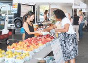 Kysha Keels buying produce from local vendor at the Johns Hopkins Farmers market at Keswick