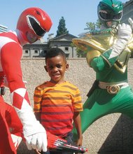 Five-year-old Savion Patterson poses with the Red and Green Power Rangers, played by Ash Naimi and Edward Estoy. The two men are known for playing popular cartoon and comic characters for events around town.