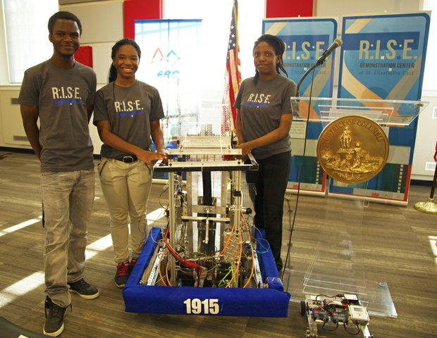 McKinley Tech High School students (left to right) Cabrel Foyet-Fokov, 17, J'Niya Butler, 15 and Angel Collins, 15  at the grand opening of R.I.S.E. Demonstration Center located at St. Elizabeths East August 13, display the robot they built.