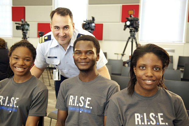 Lt. Commander John Chang of the U.S. Coast Guard Headquarters at St. Elizabeths East on August 13 with McKinley Tech students who created a robot.  Seated left to right, , J'Niya Butler, 15 , Cabrel Foyet-Fokov, 17 and Angel Collins, 15