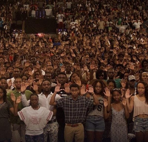 In response to the killing of Mike Brown, an unarmed teenager by a police officer, stopped for allegedly jay-walking, students of Howard University gathered in the school auditorium, with their hands up on Wednesday, Aug. 13. The photo has gone viral with the hashtag #HandsUpDontShoot.