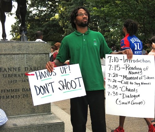Chris Stevens, 31, of D.C. holds signs during a demonstration in Meridian Hill/Malcolm X Park in Northwest D.C. on Aug. 14 to protest the killing of a black teenager in Ferguson, Missouri, earlier in the month.