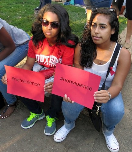 Students Shante Harvey, 21, of Southern University and Amanda Ferrara, 22, of Indiana University hold signs during a vigil at Meridian Hill/Malcolm X Park in Northwest D.C. on Aug. 14 to demonstrate against the killing of a black teenager in Ferguson, Missouri, earlier in the month.