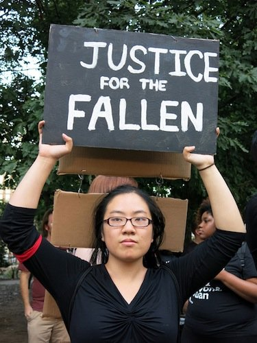 Wake Forest University student Melody Wang, 19, holds a sign during a demonstration in Meridian Hill/Malcolm X Park in Northwest D.C. on Aug. 14 to protest the killing of a black teenager in Ferguson, Missouri, earlier in the month.