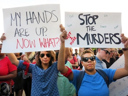 Amanda Friday, 24, and Joy Whitt, 28, holds signs during a demonstration in Meridian Hill/Malcolm X Park in Northwest D.C. on Aug. 14 to protest the killing of a black teenager in Ferguson, Missouri, earlier in the month.
