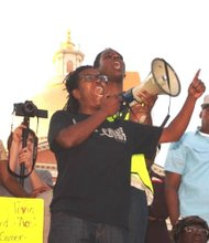 Demonstrator Lutta Neely leads a chant during Thursday's protest.