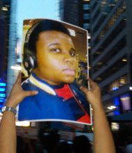 A marcher holds a picture of 18-year-old Michael Brown in Times Square