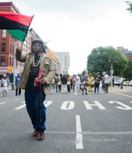 Man waves Pan-African flag as grassroots activists celebrate Marcus Mosiah Garvey's birthday. #HarlemWeek (08/17/2014)