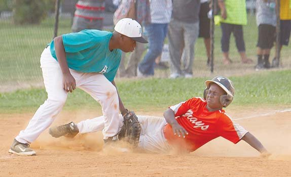 Darious Stanford covers for the Henrico Hitters as Kennedy Jones of the Hampton Grays slides safely into third base in a losing effort in the championship game of the Black World Series. The Hitters prevailed 14-4 to claim the title for 12 and under teams. Location: Parker Field Annex near The Diamond.