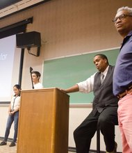 Clayton Banks and Bruce Lincoln look on as students present their app projects.