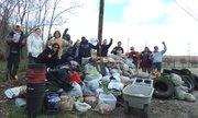 Helpers of Mother Earth volunteers stand near bags of trash and other discarded items collected in April 2013 in the area near Des Plaines and Marion streets in Joliet.