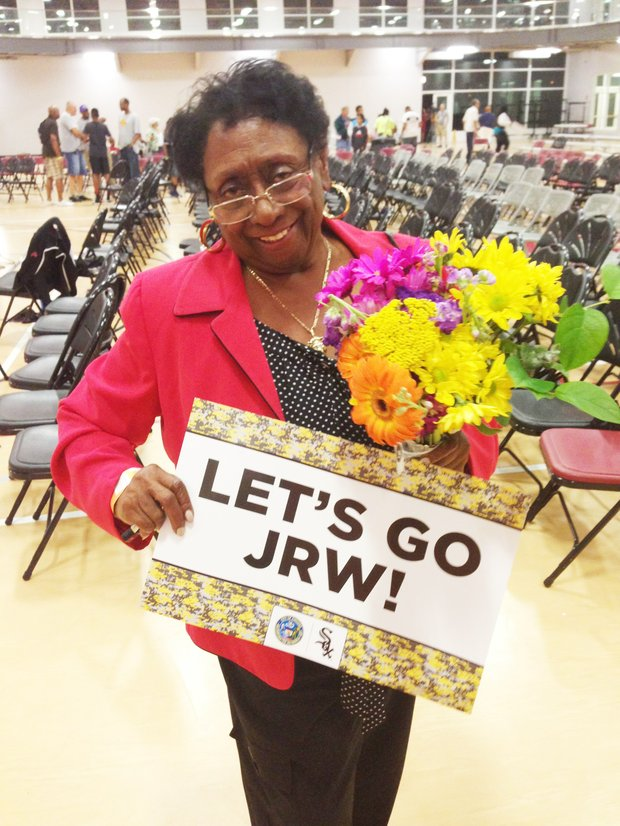 Ill. State Rep. Monique Davis (Dist.-27) was all smiles during a Jackie Robinson West Little League watch party at the Salvation Army Ray and Joan Kroc Corps Community Center,  1250 W 119th St.   Davis holds up a support sign and flowers she had for the victorious team.