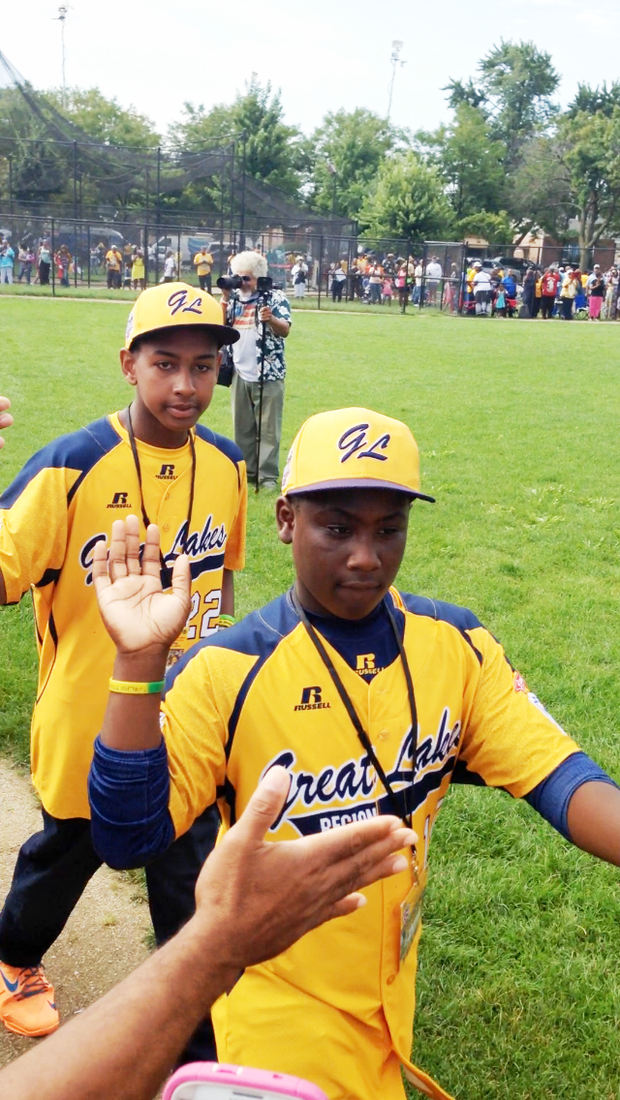 "Jackie Robinson West Little League teammates, Darion Radcliff (front) and Prentiss Luster, gives ""high fives"" to fans at Jackie Robinson Park, 10540 S. Morgan Park St., as they head to board trolley buses for a parade for the team that ended at Millennium Park in downtown Chicago for a citywide celebration after becoming Little League Baseball's 2014 World Series U.S. Champions."