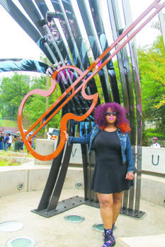 "Takesa ""KK"" Donelson, daughter of the late Chuck Brown, stands under the sculpture depicting her father at the dedication of Chuck Brown Memorial Park in Northeast D.C. on Aug. 22."