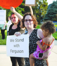 Amanda Poppy 35, holds Melody Bishop, 2, and a sign expressing solidarity with the people of Ferguson, Missouri, in front of the Washington Ethical Society in Northwest on Aug. 27.
