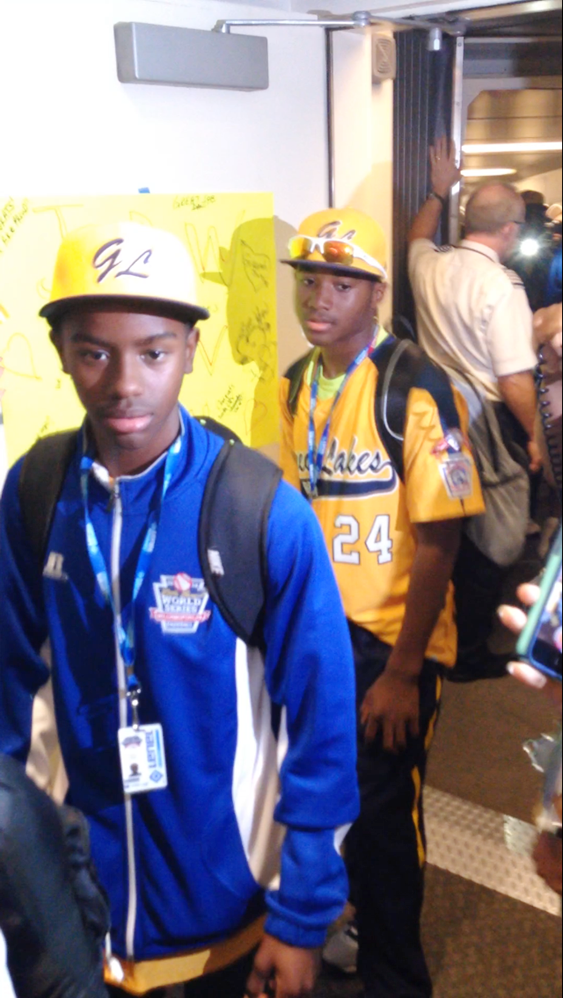 Jackie Robinson West Little League teammates, Pierce Jones and Trey Hondras take in the crowd as the exit an airplane at Chicago's Midway International Airport, 5700 S. Cicero Ave., upon returning home as Little League Baseball's 2014 World Series, U.S. Champions.