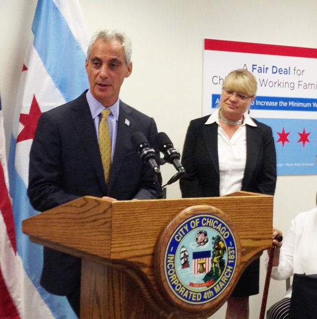 During a press conference on Sept. 3, 2014, Chicago Mayor Rahm Emanuel explains why he decided to sign an Executive Order that requires all City contractors and subcontractors to pay their employees $13 per hour.  Besides Mayor Emanuel stands Jamie L. Rhee, Chief Procurement Officer, City of Chicago.