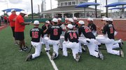 Robert Lewis, Jr. gives his team their pre-game strategy at the Pastime 18U National Championship game in Indianapolis in July. Jimmy Caruso, Manager of Baseball Operations for The BASE and one of the coaches of the 18U team looks on. Photo courtesy of The BASE.