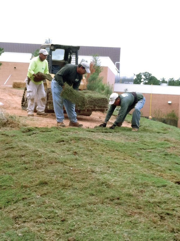 A landscaping crew begins laying sod on Thursday at Southwest DeKalb High in Decatur.