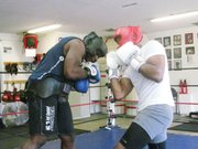 Curt Crawford (left), owner of the Curt's Ultimate Fitness and Fighting Arts,  trains one of his top prospects, Isaac Shelton, who has migrated from the boxing ring to the cage.