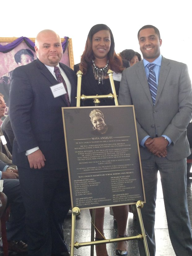L-R: Colin Ashanti Johnson, grandson of Dr. Maya Angelou; Iretha Brown, Maya Angelou Elementary School Principal; and Elliott Mathews Jones, grandson of Dr. Maya Angelou, pose for a picture in front of a plaque honoring Dr. Maya Angelou.