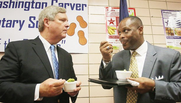 U.S. Secretary of Agriculture Thomas J. Vilsack, left, and Richmond Schools Superintendent Dana T. Bedden converse while eating broccoli Monday at Carver Elementary School.