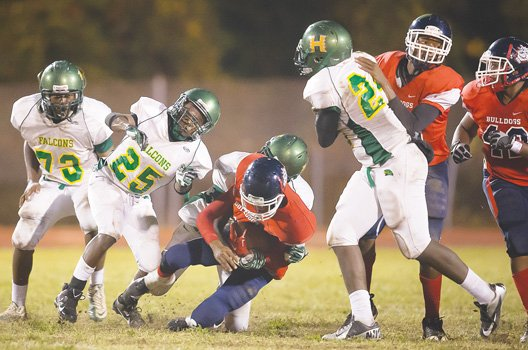 Huguenot defenders corral a George Wythe ball carrier in Friday night's game at Armstrong High School.