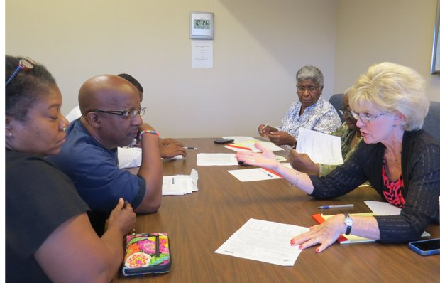DeKalb Board of Equalization member Phyllis Vann talks with Ricky and Ilane Warren during their Sept. 23 hearing on their Sept. 23 hearing on their 2014 property assessment which tripled their 2013 values.
