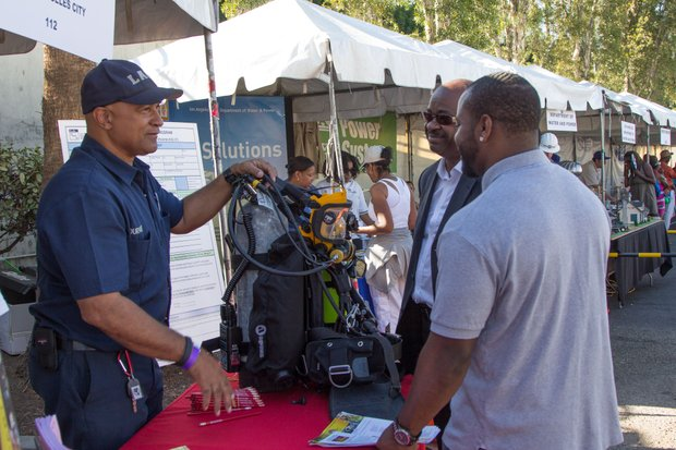 A member of United Firefighters of Los Angeles City Local 112 speaks with attendees of IBEW Local 18 and Baldwin Hills Crenshaw's Union Jobs Expo and Celebration which honored graduates of the IBEW Local 18 & Utility Pre-Craft Training Program.