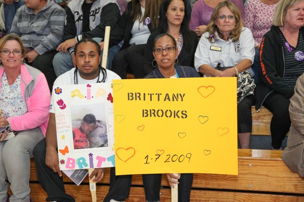 Audience members at the Take Back the Night rally Oct. 2 hold posters in memory of loved ones killed as a result of domestic violence or violent men.
