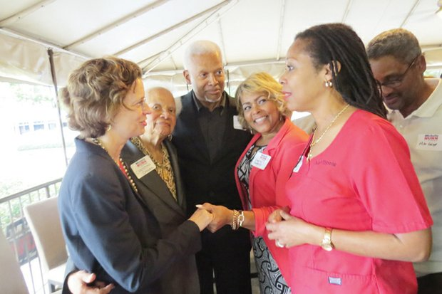 Michelle Nunn chats with Carole Moore (in pink), Tony Griggs, Debra Deberry, Congressman Hank Johnson and his mother, Christine Callier, during a stop at the Green Ginger restaurant in Decatur.