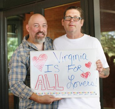 Sam Howerton, left, and Ryan Gardner, displaying their message of love, were the first male same-sex couple to buy a marriage license in Richmond.