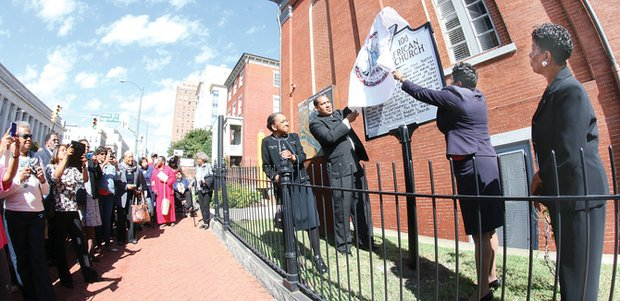 Dr. Rodney D. Waller, pastor of First African Baptist Church on North Side, unveils a state historical marker commemorating one of the city's oldest black churches. An appreciative audience watches the ceremony at the original site of the church.