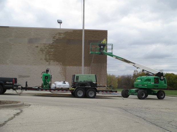 A worker cleans the exterior masonry of the former Cub Foods store, which is being converted into a new church for the Harvest Bible Chapel Joliet.