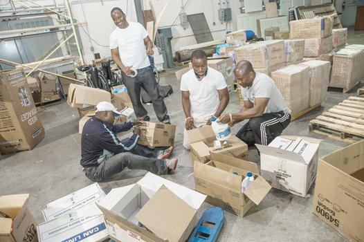 From left, Garway Bright, Othello Dixon, Charles Jallah and Joseph Jones pack food and medical supplies for Virginians in Action for Liberia Against Ebola. The supplies are being shipped from a Chesterfield County warehouse to counties in Liberia most affected by the Ebola outbreak.