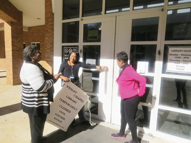 From left, children's librarian Mia Buggs (from left), branch manager Peggy Ramsey-May and circulation supervisor Jeannine Jones removed the closed sign Thursday.