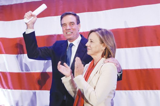 U.S. Sen. Mark Warner waves to the crowd with his wife, Lisa Collis, at an election party in Arlington.