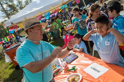 Andrės Valverde makes an oragami bird for 10 year old Cosme Salazar at the 2014 Imagine Festival.