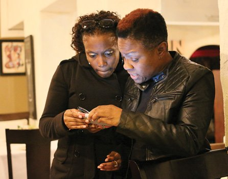 "Radio personality ""Miss Community"" Clovia Lawrence, right, and Ebony Leach peruse poll results Tuesday night at an election night gathering at Southern Kitchen in Shockoe Bottom."