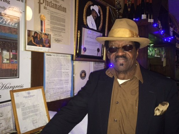 Samuel Hargress Jr. in front of the awards wall at Paris Blues