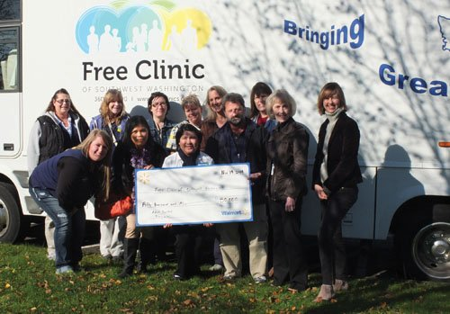 Representatives of the Free Clinic of Southwest Washington accept a donation of $50,000 from Walmart as a group of associates ...